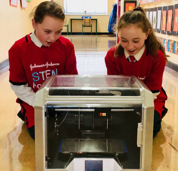 Twins Ami and Mia, students of Scoil Mhuire Ballincollig, with the 3D printer that has been provided to the school by DePuy Ireland as part of its new Virtual STEM Academy.