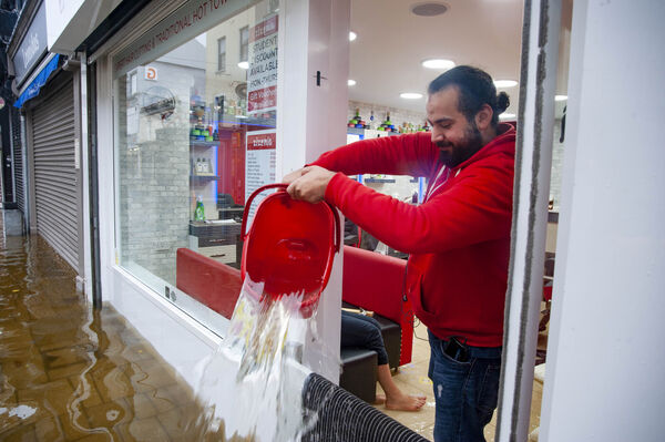 Staff clean up in Zizenia Barbers during heavy flooding on Oliver Plunkett street, Cork city.
