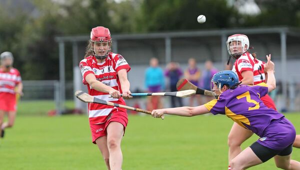 Fiona Keating, Courcey Rovers, drives the sliotar down the field past Carolyn Motherway, St Catherine's. Picture: Jim Coughlan.