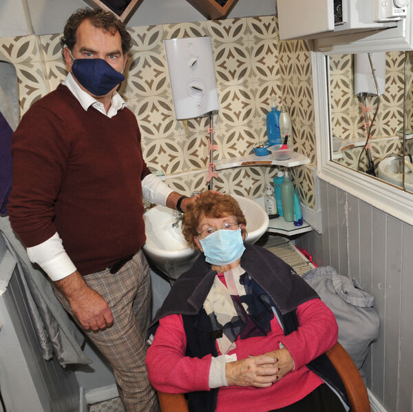 Joseph Byrne of Joseph's Hair and Beauty Salon, Glasheen with regular customer Pauline Scanlon prior to the start of a 6-week closure for the Level Five Living with Covid-19 Coronavirus public health measures during the global pandemic 2020.