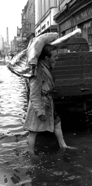 DEEP TROUBLE: Socks and shoes are off as floods hit Cork city in December 1955