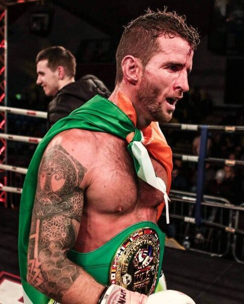 Muay Thai fighter Sean Clancy with his belt and the Irish flag after a successful fight.