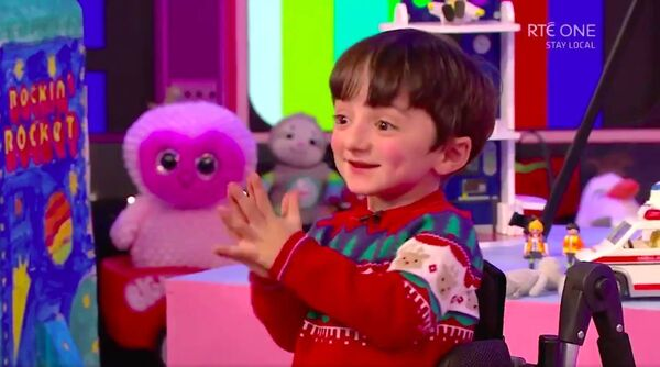 Adam King clapping in delight as he sees his favourite hospital porter, John Doyle on the Late Late Toy Show