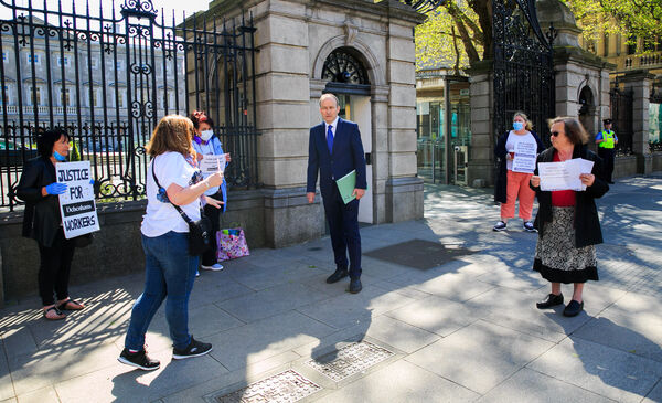 Fianna FAil leader Micheal Martin speaks to Debenhams staff during a protest by Debenhams workers at Leinster House on Kildare Street Dublin in July.