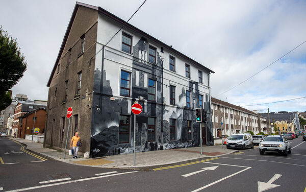 A man walking past the Middle Parish Community Centre on Grattan Street, Cork, where artist Peter Martin created a mural depicting the burning of Cork taking from an old Irish Examiner picture. Picture Dan Linehan