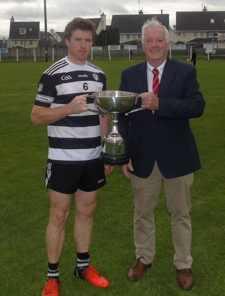 Chairman of the East Cork Board Donal O'Keeffe presents the Jim Ryan Cup to Midleton vice Captain Seamus O'Farrell.
