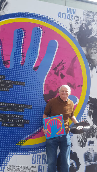 Pictured at the new artwork outside the City Library is Ricky Dineen of Nun Attax with one of the original Kaught at the Kampus records from 1980. Pic: Siobhan Bardsley