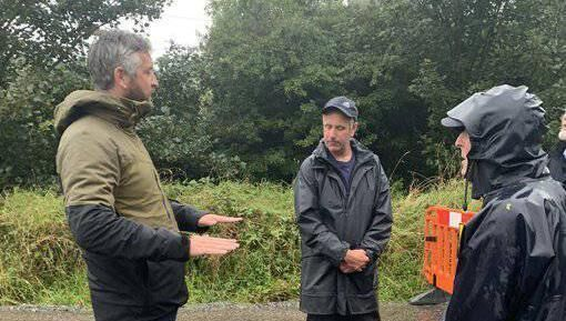 Deputy Christopher O'Sullivan talks with residents near Glandore during an inspection of flood damaged roads on Thursday.