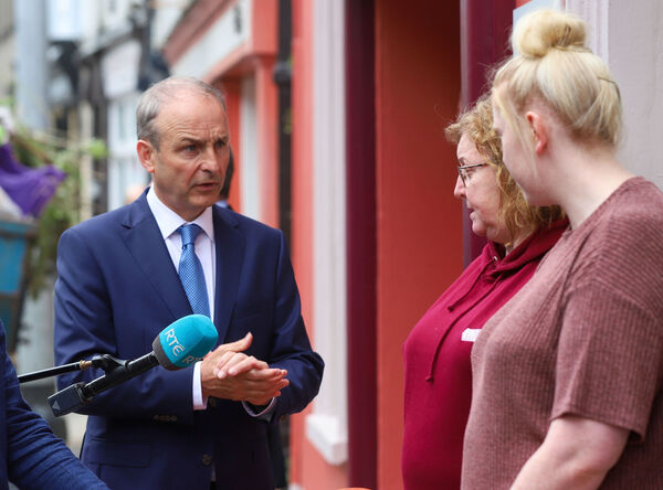 An Taoiseach Micheal Martin speaks with the operators of the Eldon Hotel on Bridge street, Skibbereen, which was severely damaged in storm Ellen. Photo: Damien Storan/PA Wire