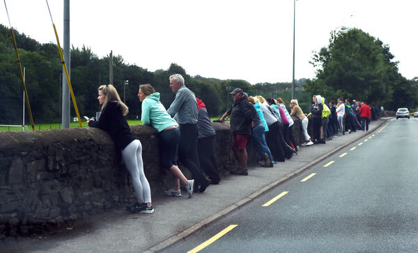 Supporters and onlookers watch the game over the wall in Glanmire. Picture: Eddie O'Hare