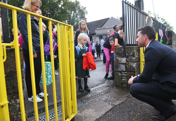 First day at school for junior infant pupils arriving at Scoil Iosaf Naofa, Ballintemple NS, Crab Lane, Cork on Thursday 27th August 2020.Luna O'Regan is welcomed to 'big school' by Principal Bryan McCarthy, at the school gate.Coronavirus covid-19 global pandemic 2020.Pic; Larry Cummins