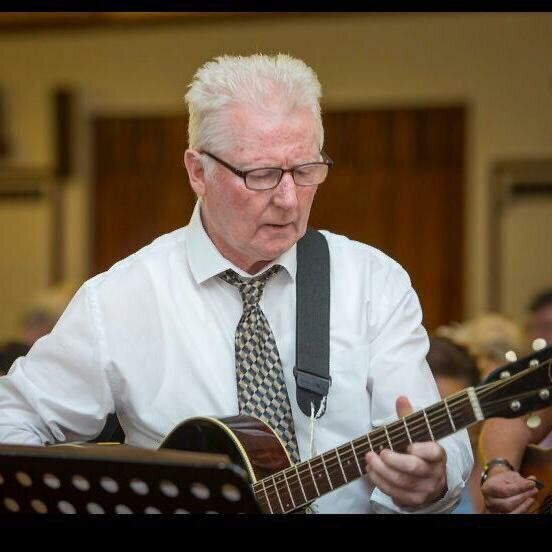Sean O'Leary playing guitar with the Knocknaheeny Holyhill folk group.