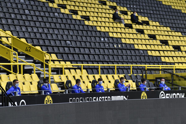 Schalke substitutes sit two metres away from each other on the bench in the empty Dortmund Stadium. Yet minutes later, many would have physical contact with teammates and opponents when they took to the field to play.