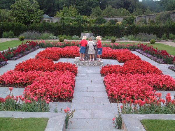 Inquisitive children inspect the contents of a large urn in the Italian garden at Fota Arboretum, Cork.