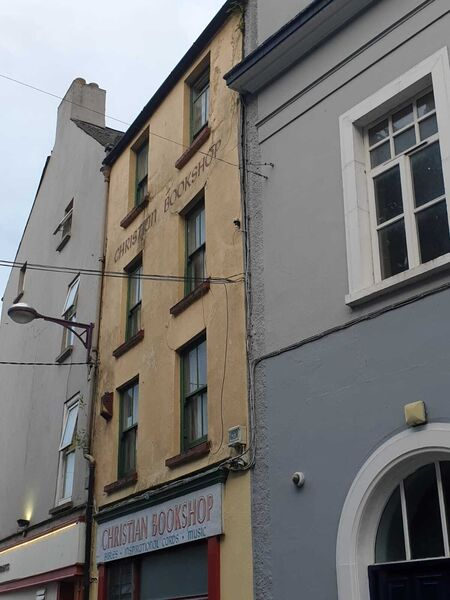 The side of the Cork Christian Bookshop where the plaster is coming away from the wall.