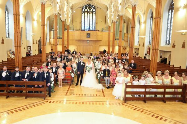The couple with their family and friends at the North Cathedral on their wedding day. Their reception was hosted in the Oriel House Hotel, Ballincollig.