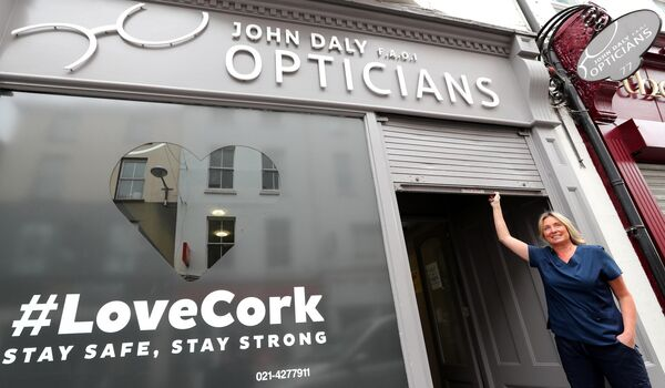 Clodagh Daly, John Daly Opticians, lifting the shutter to re-open the business.