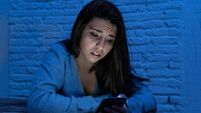 Dramatic portrait of sad scared young woman on smart mobile phone suffering cyber bullying and harassment. feeling lonely, depre
