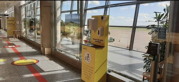Sanitation station at Cork Airport along with floor marking reminding people to socially distance.