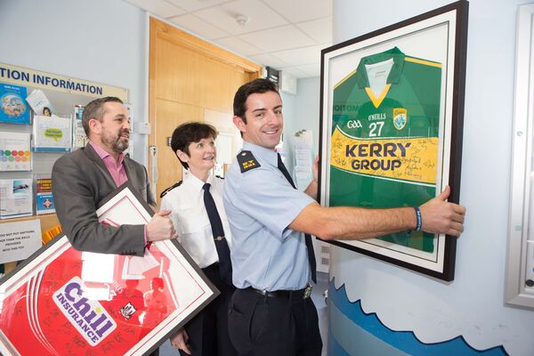Michael Sheridan, Mercy University Hospital Foundation, Assistant Garda Commissioner Anne-Marie McMahon and Garda Aidan O'Mahony hanging signed Cork and Kerry GAA Jerseys in St Anne's Ward, Mercy University Hospital, in 2017. Picture: Darragh Kane