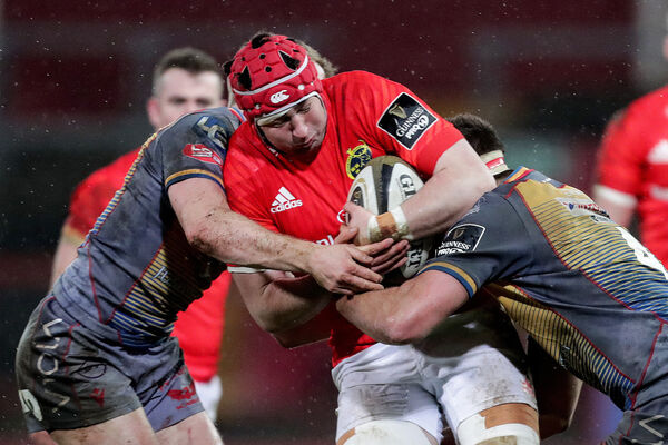 Munster's John Hodnett is tackled by Jonathan Evans and Lewis Rawlins of the Scarlets. Picture: INPHO/Laszlo Geczo