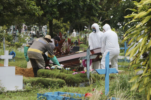 Funeral workers in protective clothes, and cemetery workers, place the coffin of Robson de Souza Lopes into his grave site the Parque Taruma cemetery in Manaus, Brazil.