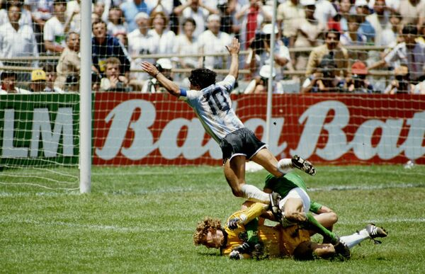Diego Maradona of Argentina goes flying over the challenges of West German goalkeeper Harald Schumacher and defender Karl Heinz Foerster. Picture: Mike King/Getty Images