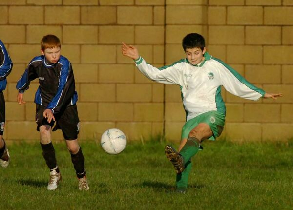Greenwood's John Egan clearing the ball past Wilton United's Damian Roche during the under 13 Schoolboys National Cup in Togher. Picture: Richard Mills.