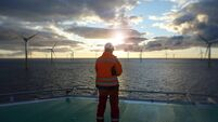 Offshore manual worker standing on helipad with wind-turbines behind him in sunset