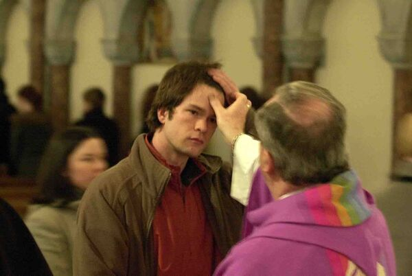 Fr Joe Coughlan puts ash on the foreheads of students at the Honan Chapel on Ash Wednesday, 2004. Pic: Gavin Browne