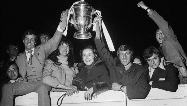 Cork Hibs captain Dave Bacuzzi, right, holding the FAI Cup with hat-trick hero Miah Dennehy amid a group of jubilant supporters following his team's 3-0 win over Waterford at Dalymount Park in 1972.