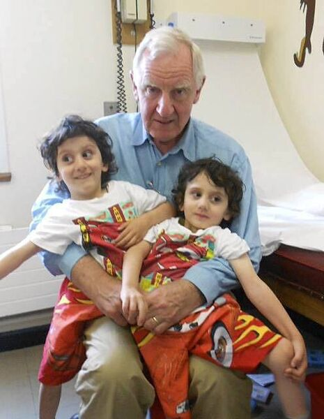 Mr. Edward Kiely with Hassan and Hussein Benhaffaf, whom he separated as conjoined twins.