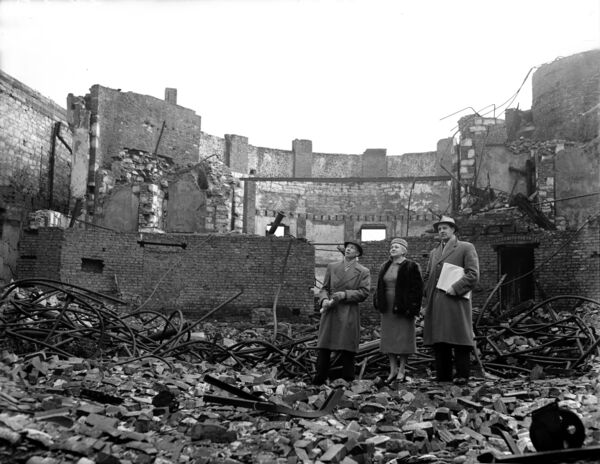 Please archive -Group of women standing in the ruins of the former Opera House after the fire.
