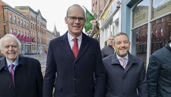 Simon Coveney and Jerry Buttiner arriving to hand in their nomination papers to the returning officer Martin Harvey in Cork. Photo: Billy MacGill.