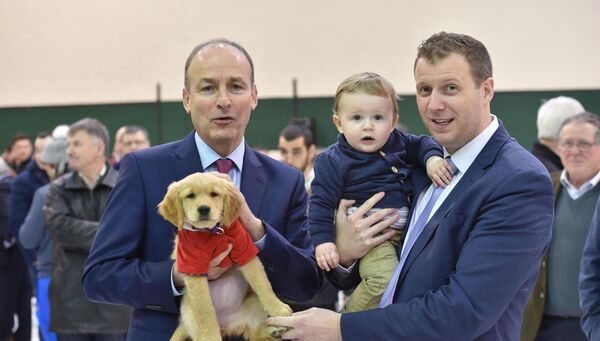 Micheál Martin TD holding Magic the dog with Padrig O'Sullivan and his son Páidí at the count centre at Nemo Rangers GAA club, Cork. Picture Dan Linehan