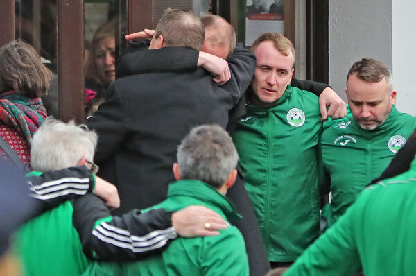 Andrew McGinley is hugged during the funeral service for his three children. Photo credit: Niall Carson/PA Wire