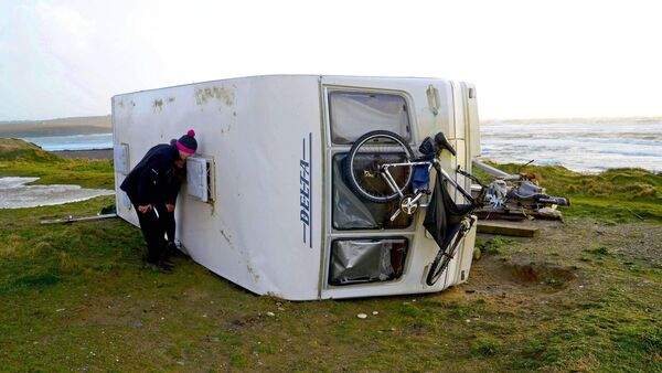 A caravan rests on its side near the beach at Garretstown Co Cork after being blown over in Storm Brendan. Picture Denis Boyle