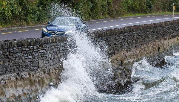 Storm Atiyah hit West Cork this afternoon with winds up to 100kmh. A car drives along the N71 into Bantry as big waves breach the sea wall. Picture: Andy Gibson.