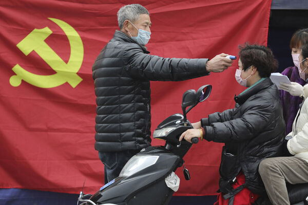 A volunteer stands in front of a Communist Party flag as he takes the temperature of a scooter driver at a roadside checkpoint in Hangzhou in eastern China's Zhejiang Province.