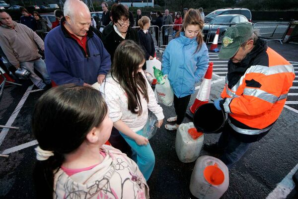 A county council worker distributing water amongst people at Ballyvolane shopping centre. Picture: Cillian Kelly