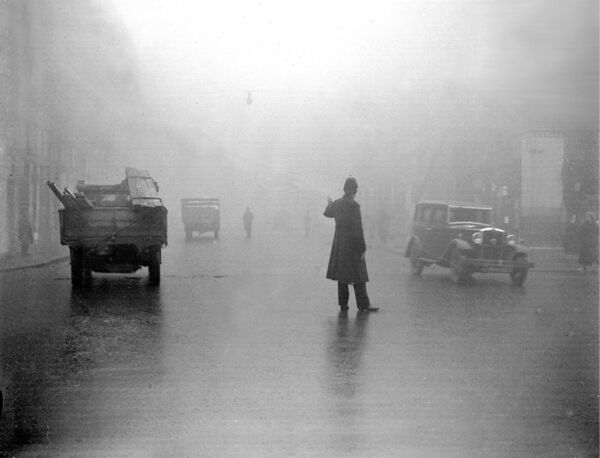 A Garda attempts to direct traffic in heavy smog at Singer's Corner, Cork 1934.