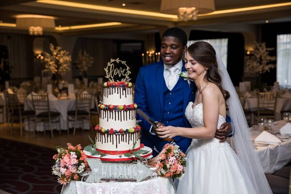 CELEBRATING THEIR LOVE: Gosia and Fletcher cutting their wedding cake, at their reception in the Midleton Park Hotel.