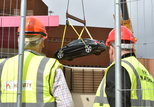 One of the first cars is hoisted from the car park on the roof of Douglas Village Shopping Centre, Douglas, Cork which was damaged by a large fire last weekend. Picture Dan Linehan