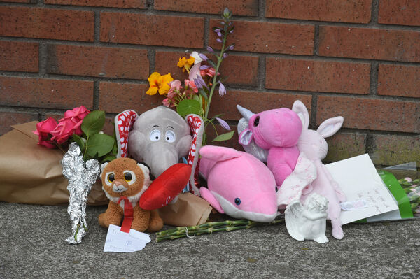 Flowers and stuffed toys as tributes at the scene.Pic; Larry Cummins