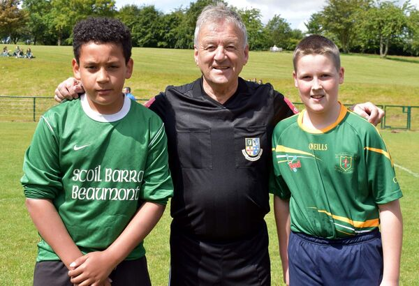 Referee Pat Kelly, with captains, Tyrese Sonowo, Scoil Barra and Andrew Maume, Ballintemple NS, prior to the Slim Jim McCarthy Cup final.Picture: Mike English.