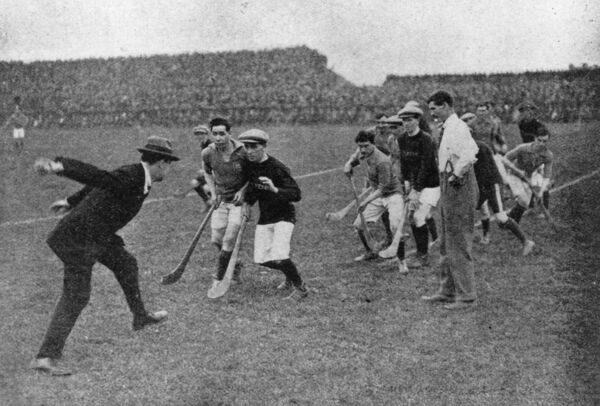 1921: Sinn Fein leader and Commander-In-Chief of the Irish Free State Army Michael Collins (1890 - 1922) throwing in the ball to start a hurling match at Croke Park, Dublin.