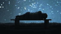 A man sleeping on a bench. Forest and starry sky bokeh In the background.