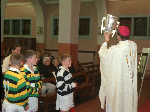 Bishop John Buckley accepts the Liam McCarthy Cup during the offering of gifts at the Mass for the late Jack Lynch at the Church of the Annunciation, Blackpool.