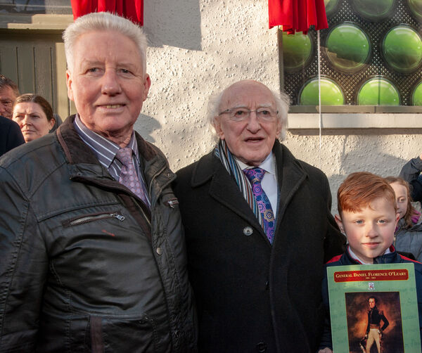 President Michael D Higgins with Richard Lynch, president of the Daniel Florence O'Leary Assoc and his son Emmet at the unveiling of a plaque outside Broderick's Pharmacy on Barrack Street, Cork, commemorating the birthplace of Daniel Florence O'Leary. Pic: Brian Lougheed