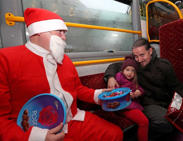 Retired Bus driver, Michael Howick, as Santa with Emily Belle McCarthy and her dad, Trevor McCarthy, from Wilton. Picture: Jim Coughlan